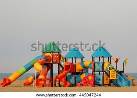 Coloured children playground on beach - stock photo