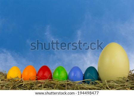 coloured easter eggs in hay and straw