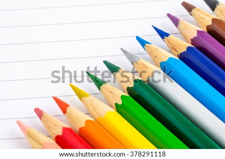Coloured Pencils Lying on a Notebook. Back to School Concept. Shallow Deep of Field