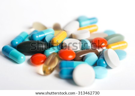 Coloured pills and capsules on white background. - stock photo