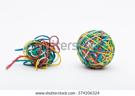 Coloured rubber band ball next to messy pile