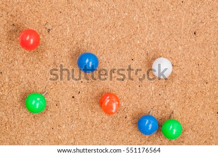 coloured thumbtack pins on brown cork pinboard