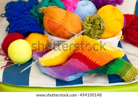 Coloured wool yarn into skeins and tangles. Bright yarn for knitting lying on a green chair.