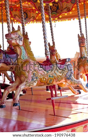 Colourful and brightly patterned wooden horses on a carousel - stock photo