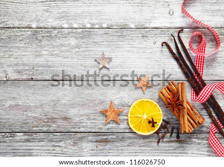 Colourful array of decorative Christmas spices with a fresh red and white checked twirled ribbon on a background of grungy textured weathered white wood - stock photo