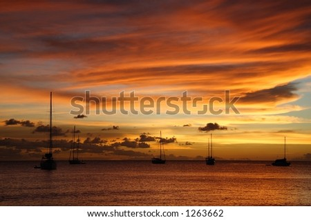 Colourful caribbean sunset with sailboats - stock photo