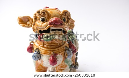 Colourful ceramic ancient lion mythical creature statue. Symbol of luck and prosperity for chinese and asian sculpture. Shot with natural light. Slightly defocused and close-up shot. Copy space.