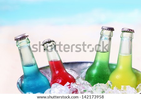 Colourful chilled soda drinks in unlabeled glass bottles standing in a metal container of crushed ice cubes for a summer party - stock photo
