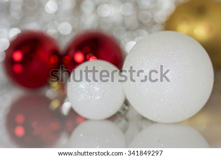 Colourful christmas baubles against a bokeh background.