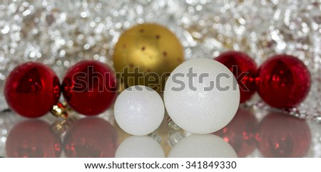 Colourful christmas baubles against a silver bokeh background - stock photo