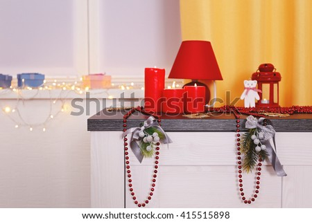 Colourful Christmas decorations and candles on the table against window decorated with glowing lights, close up - stock photo