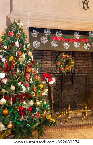 Colourful Christmas tree standing on flagstones in front of a large open granite hearth decorated with a Merry Christmas garland and snowflakes. Warm ambient interior light and copy space above - stock photo