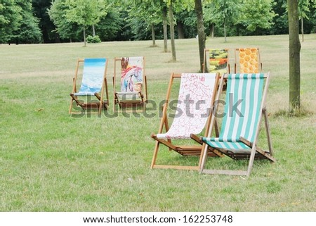 colourful deck chairs in park on grass - stock photo