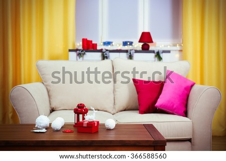 Colourful decorated interior. Comfortable living room, table with Christmas decorations on it is close up - stock photo