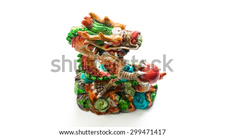 Colourful dragon with ball figurine. Concept of feng shui for good luck. Isolated on white background. Slightly de-focused and close-up shot. Copy space.