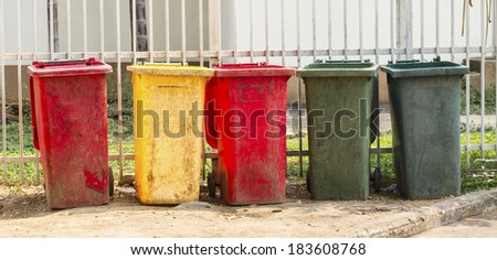 colourful dustbins in the public area of a port - stock photo