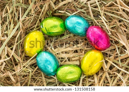 Colourful easter eggs in a circle on straw