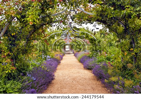 Colourful English summer flower garden with a path under archway - stock photo