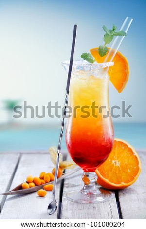 Colourful exotic Tequila Sunrise cocktail served on the rocks with crushed ice and a swizzle spoon - stock photo