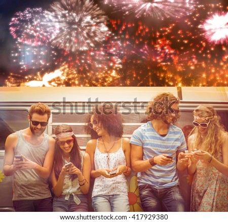 Colourful fireworks exploding on black background against hipster friends using their phones - stock photo