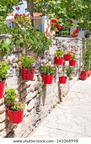 Colourful flower pots and flowers on a stone wall - stock photo