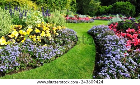 Colourful Flowerbed and Grass Path in a Beautiful Garden - stock photo