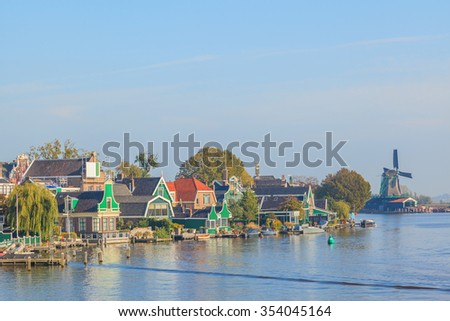Colourful houses with dutch windmill in Zaaneschans, Netherland - stock photo