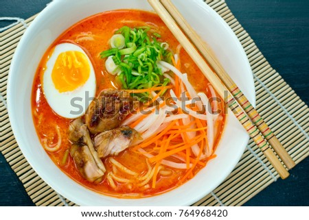 Colourful image of red ramen, a traditional Japanese noodle soup served with chicken, chives and hard boiled egg in a white bowl