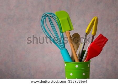 colourful kitchen utensils in green bucket - stock photo