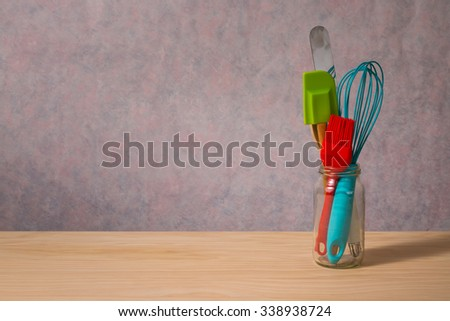 colourful kitchen utensils on wooden table - stock photo