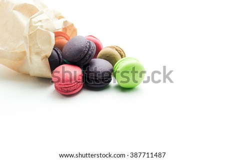 Colourful macaroons Out of a paper bag on white background