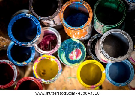 Colourful paint cans on the floor viewed from above