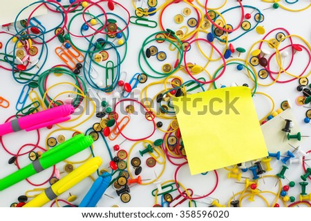 Colourful paper clips, elastic rubber bands, markers, drawing pins thumb tacks and sticky notes as a texture background. Office concept.