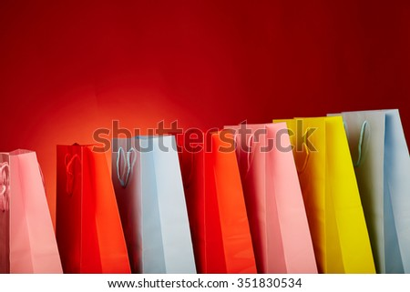 Colourful paper shopping bags isolated on red