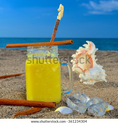 Colourful pineapple-cinnamon cocktail served on a golden beach at a tropical holiday resort during an enjoyable summer vacation - stock photo
