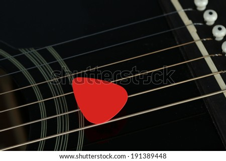 Colourful plectrum on guitar, close up - stock photo