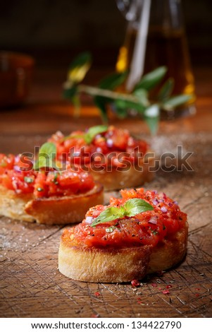 Colourful red tomato bruschetta on slices of crisp crusty toasted or grilled baguette lying on an old grunge badly scored wooden chopping board, low angle view with copyspace