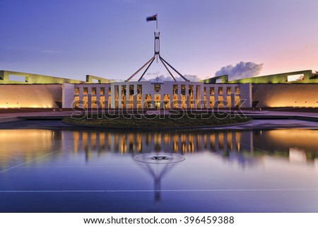 colourful reflection of Canberra's new parliament building in a fountain pond at sunset. - stock photo