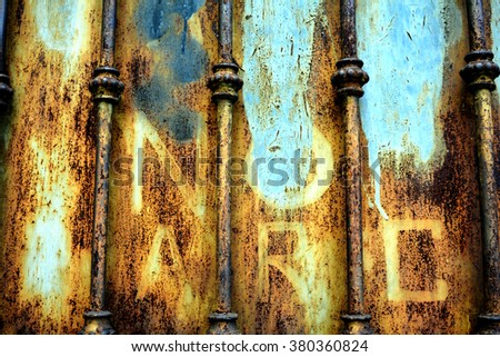 Colourful rusty gate with faded lettering