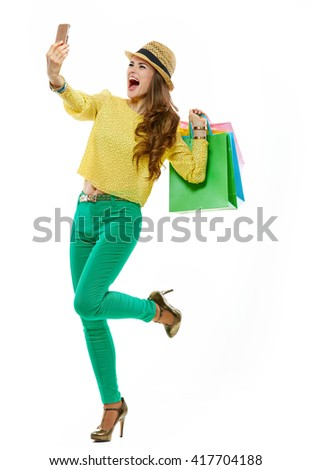 Colourful shopping vibes. Full length portraits of cheerful brunette woman in hat and bright clothes with shopping bags taking selfie - stock photo