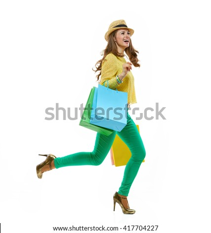 Colourful shopping vibes. Full length portraits of smiling brunette woman in hat and bright clothes with shopping bags running