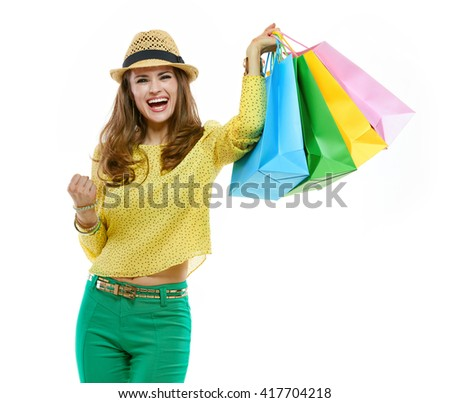 Colourful shopping vibes. Happy brunette woman in hat and bright clothes with shopping bags rejoicing - stock photo