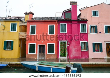 Colourful small houses and the canal with boats on a rainy day in Burano island, Venice, Italy. March 3, 2016