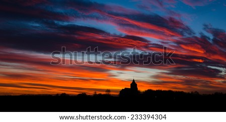 Colourful sunset behind a church (silhouette) - stock photo