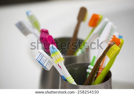 colourful tootbrushes in family bathroom - stock photo