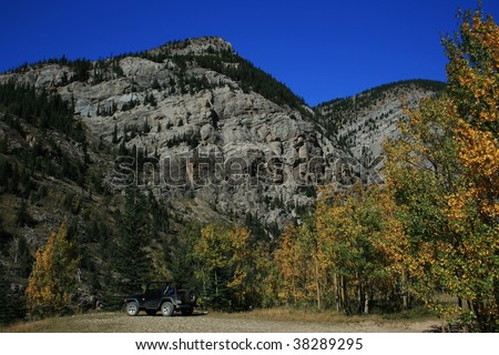 Colourful trees against rocky mountain; parked jeep; autumn/fall; bright blue sky; Alberta, Canada - stock photo