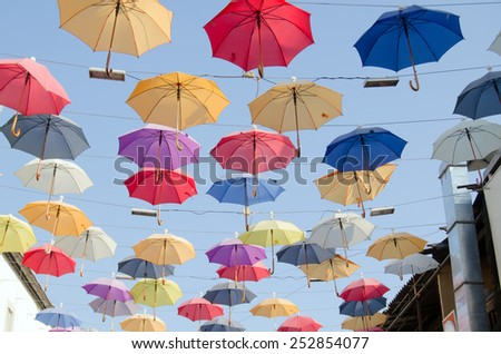 Colourful umbrellas danging over the top of a bazaar street popular for its restaurants and cafes in the historic district of Antalya, Turkey.