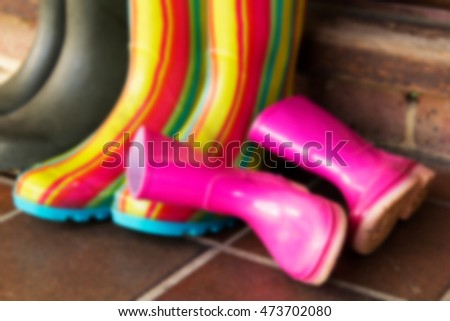 Colourful wellington boots left outside on a doorstep Out of focus.