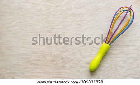 Colourful whisk or multi color egg beater on empty wooden surface. Concept of kitchen tool for kids or young chef. Slightly de-focused and close-up shot. Copy space. - stock photo