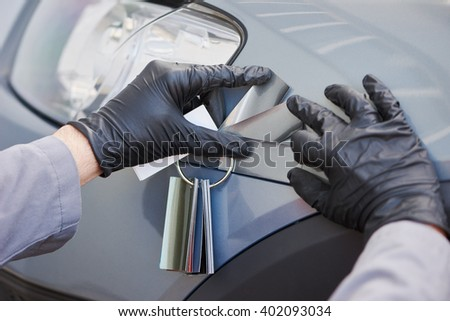 colourist man selecting color of car with paint matching samples - stock photo